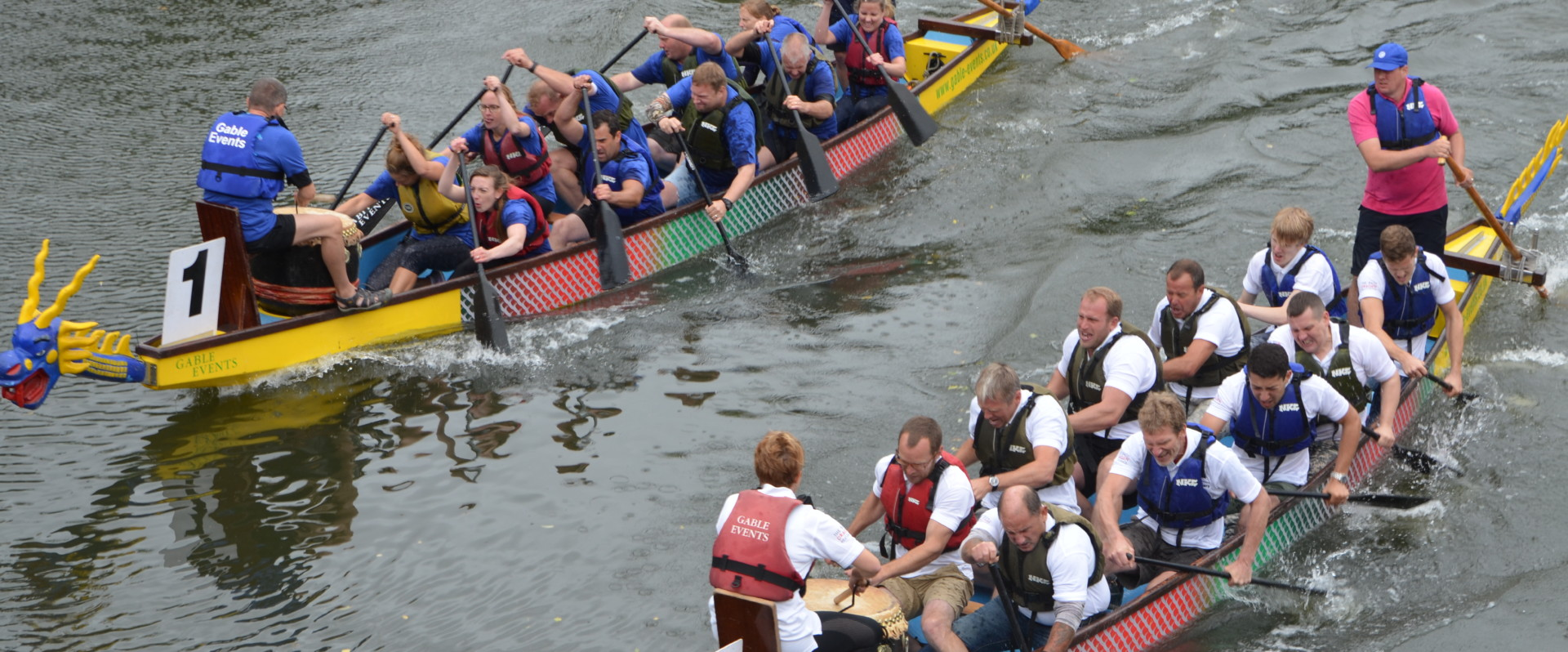 Two groups of people in dragon boats on the river