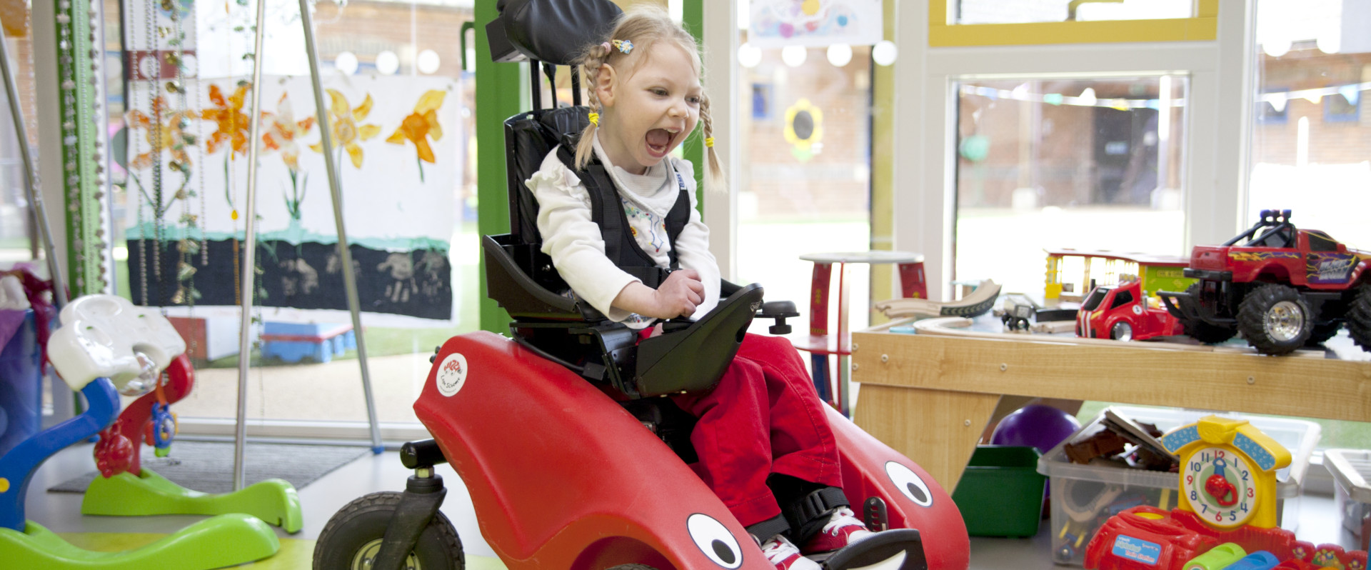 Little girl rides Wizzybug in playroom