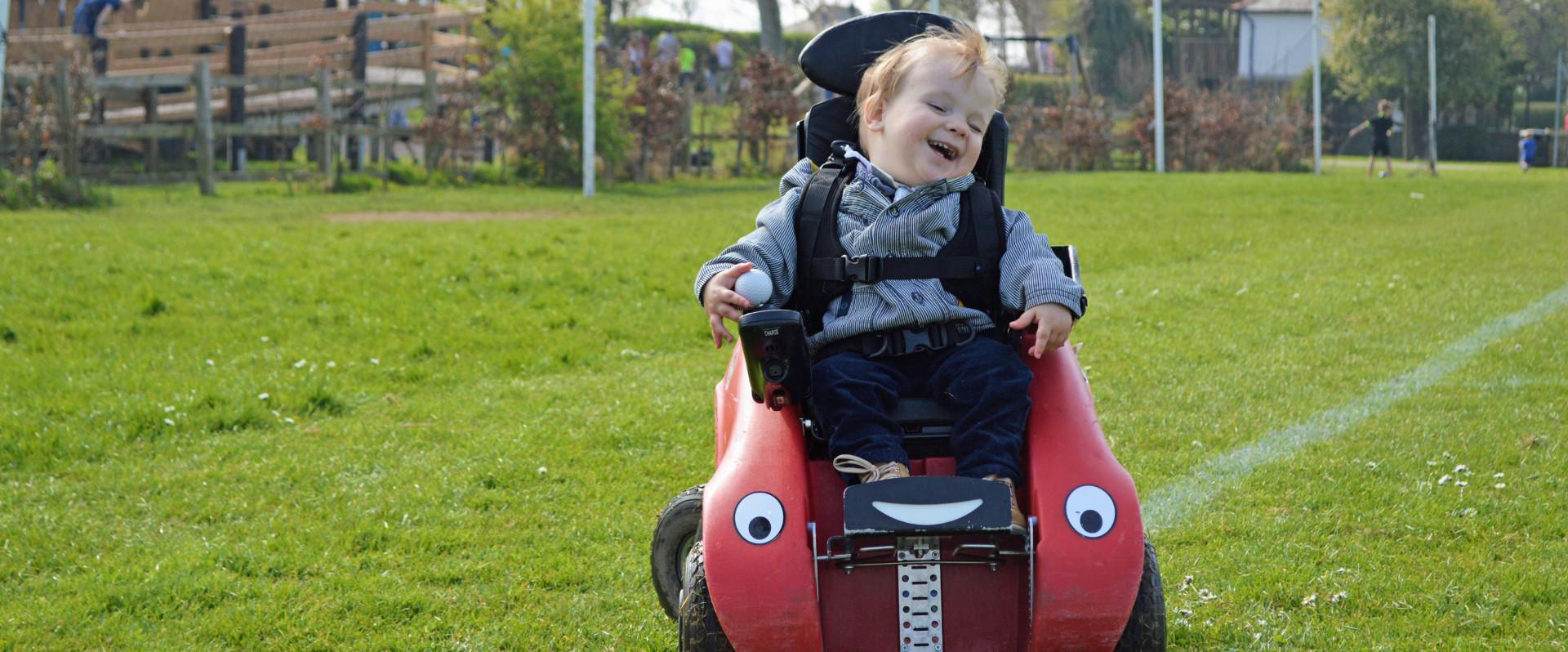 Happy boy in Wizzybug in a park