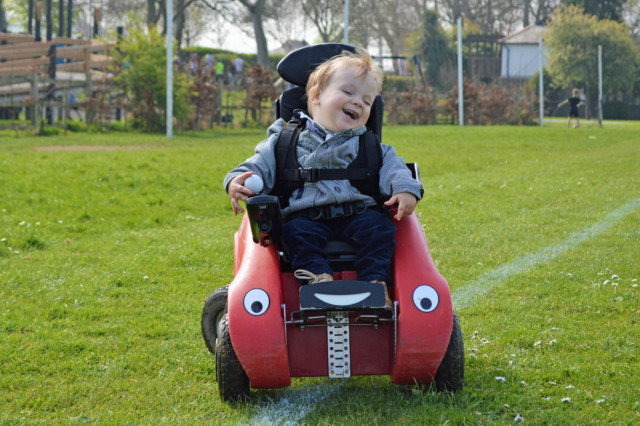 Happy boy in Wizzybug in a park