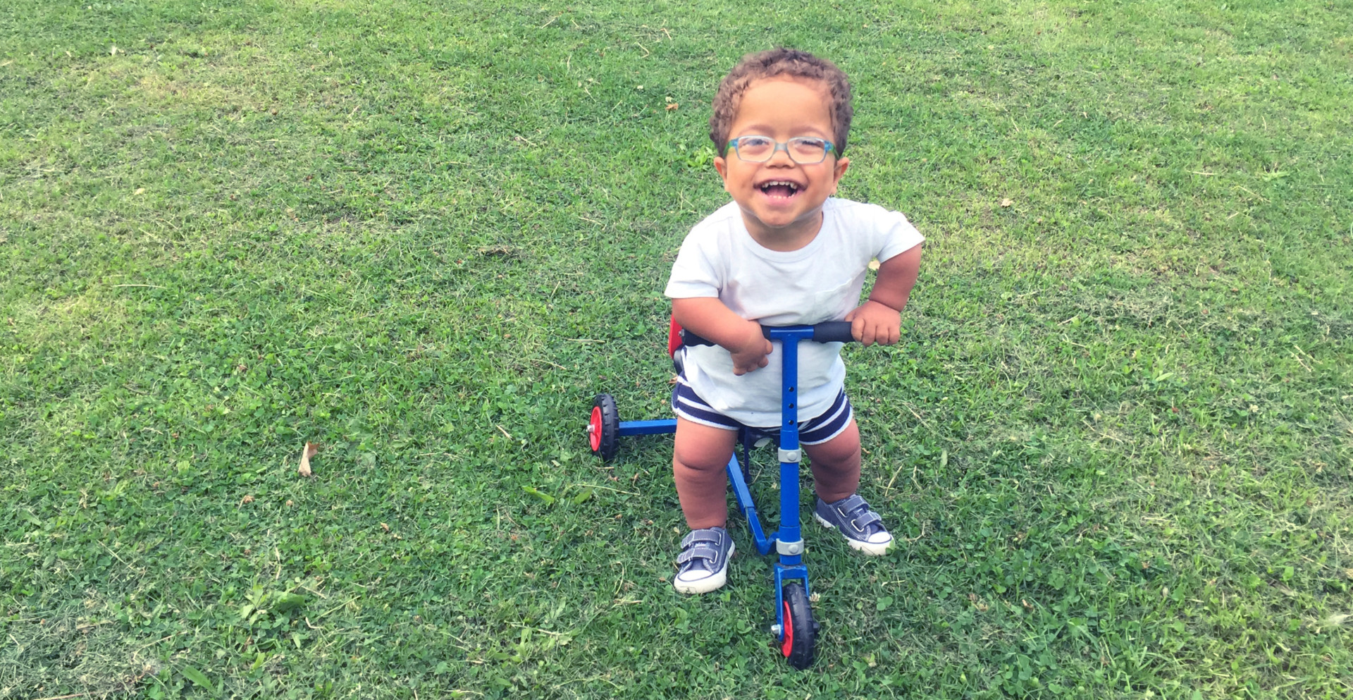 Freddie in a field with his Sit 'n' Ride tricycle