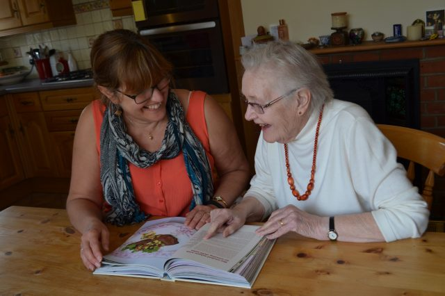 A woman at the dining table looking at a cookbook with her mother
