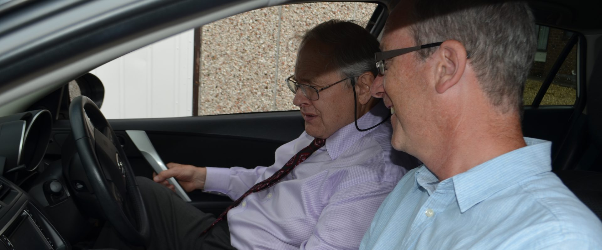 Showing an older gentleman the controls in a car