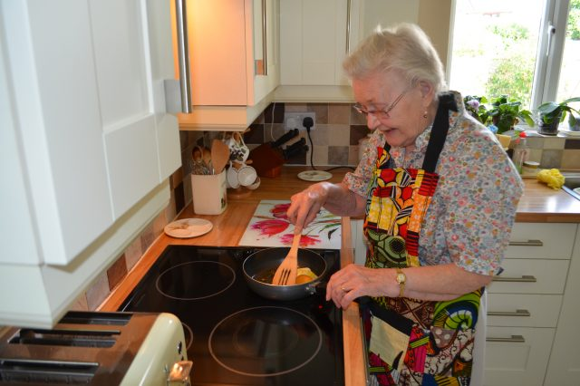 Older lady cooking in her kitchen at home