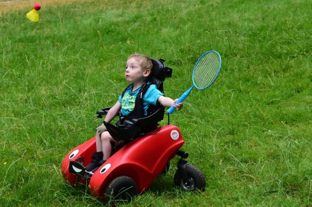 Little boy playing bat and ball while sat in his Wizzybug