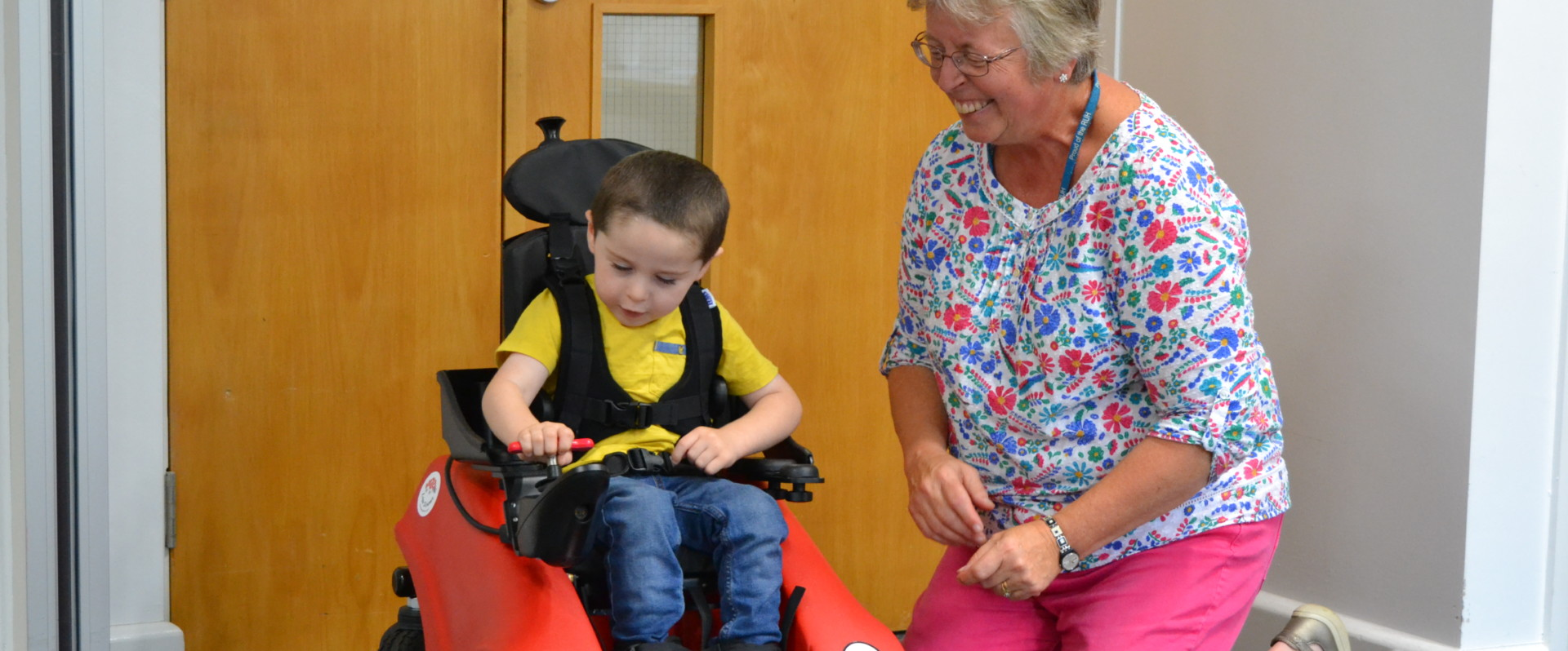An occupational therapist helps a little boy learn how to use a Wizzybug