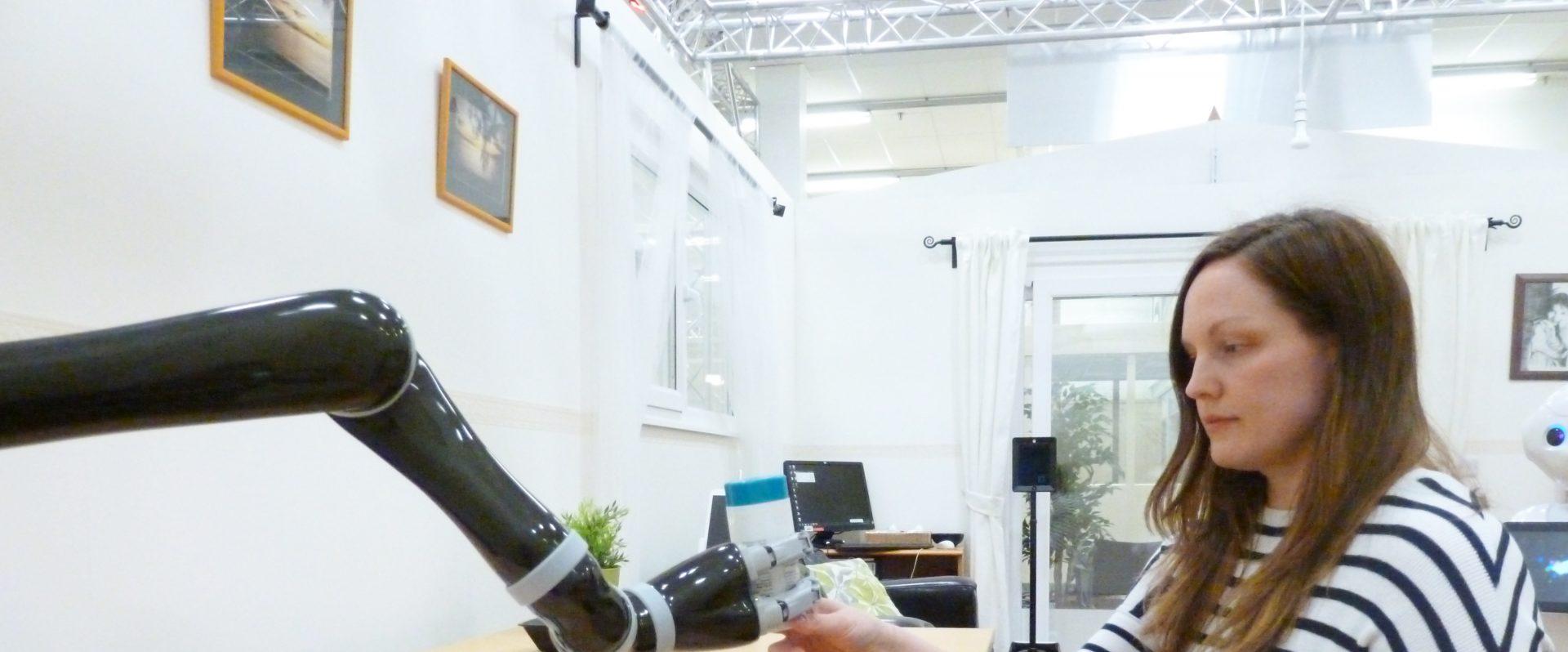 A robotic arm handing a woman an object