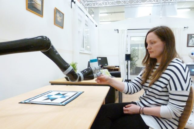 A robotic arm handing a woman an object