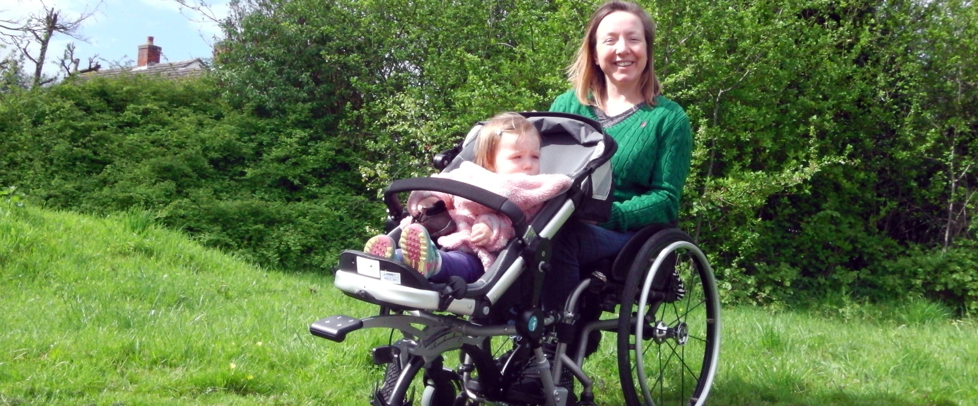 A mother using her wheelchair with her daughter in the wheelchair baby carrier