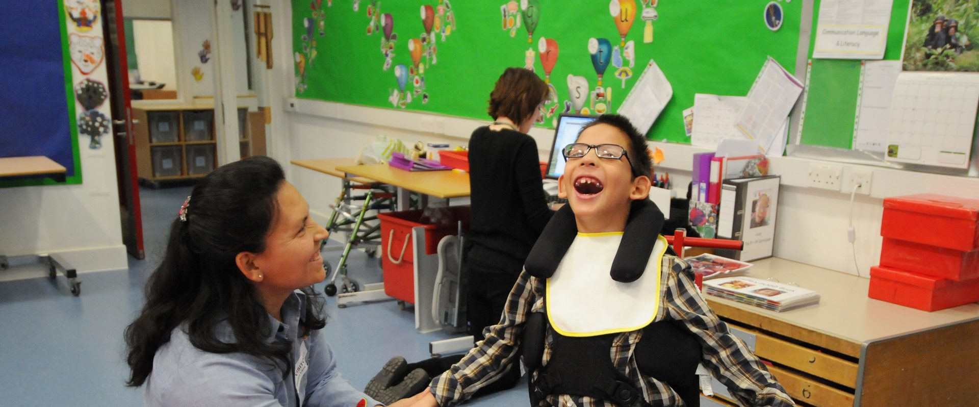 A boy with cerebral palsy smiles in our dynamic seat as his mother looks on smiling