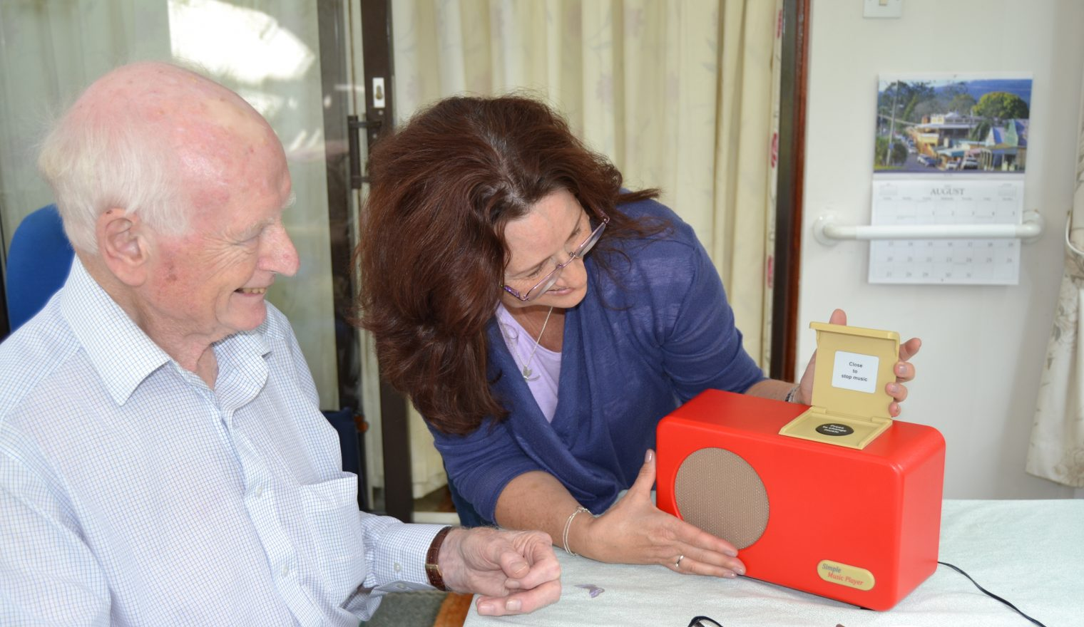 An older man with his daughter looking at the Simple Music Player