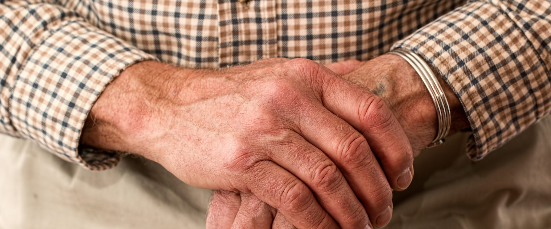 Close up of older gentleman's hands and walking stick