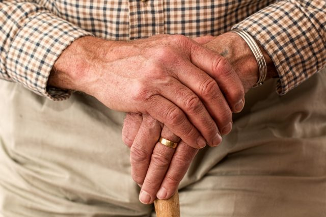 Close up of older gentleman's hands and walking stick