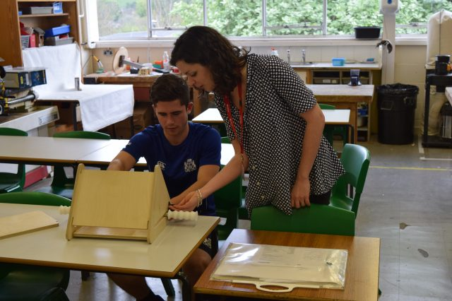 A designer guides a student through his prototyping