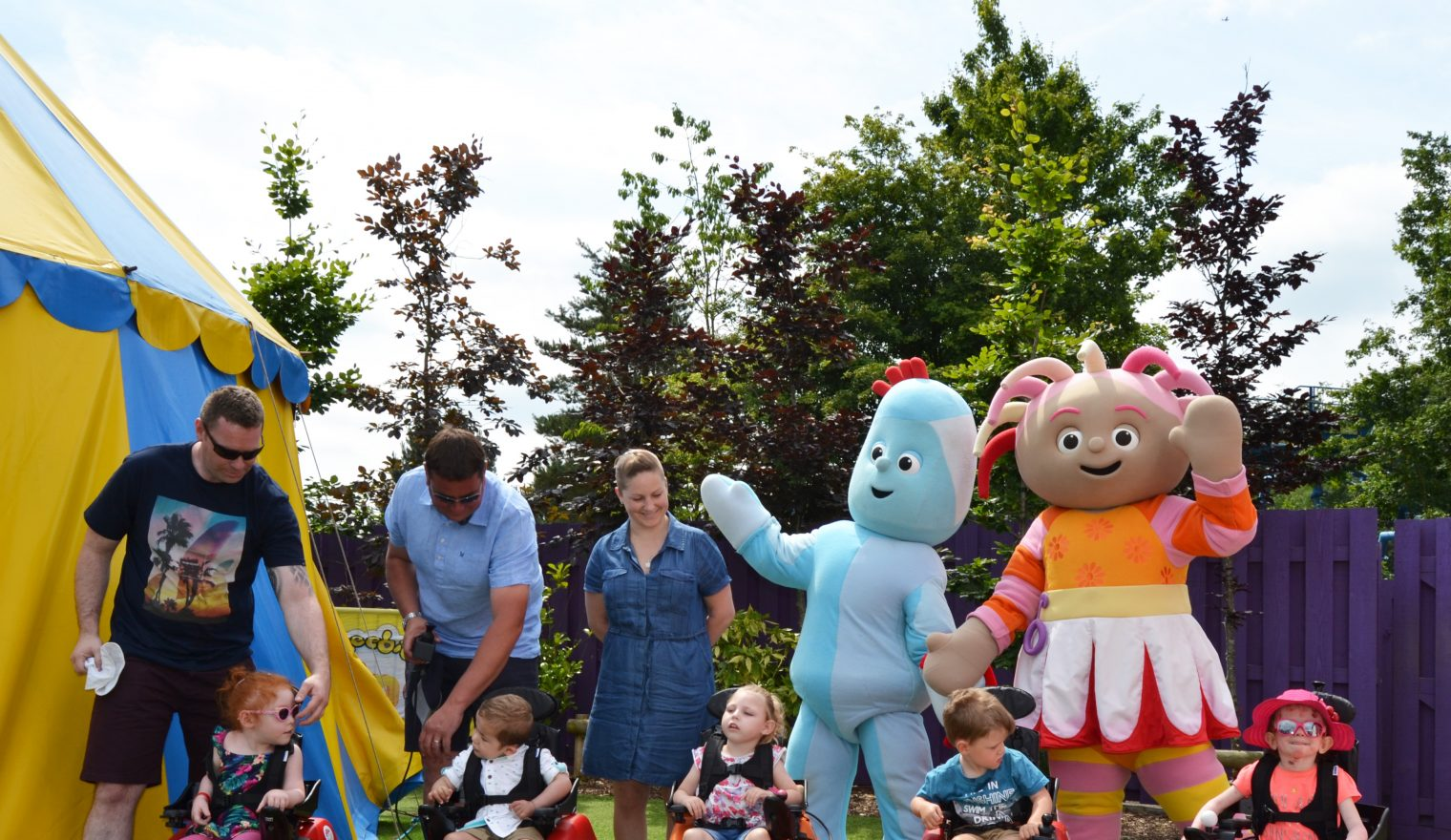 Five children in Wizzybug powered wheelchairs posing with characters at CBeebies Land