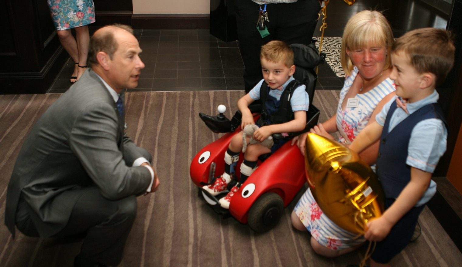 Prince Edward crouching down to speak to two children and their mum