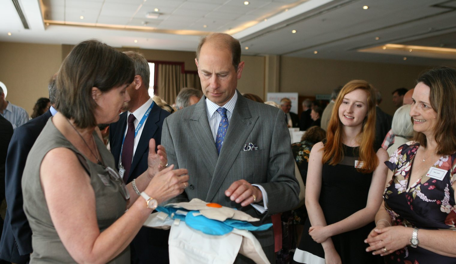 A woman showing a sensory cushion to Prince Edward