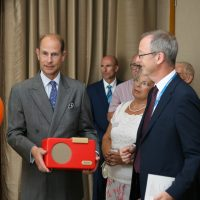 Prince Edward holds a Simple Music Player with several people stood beside him