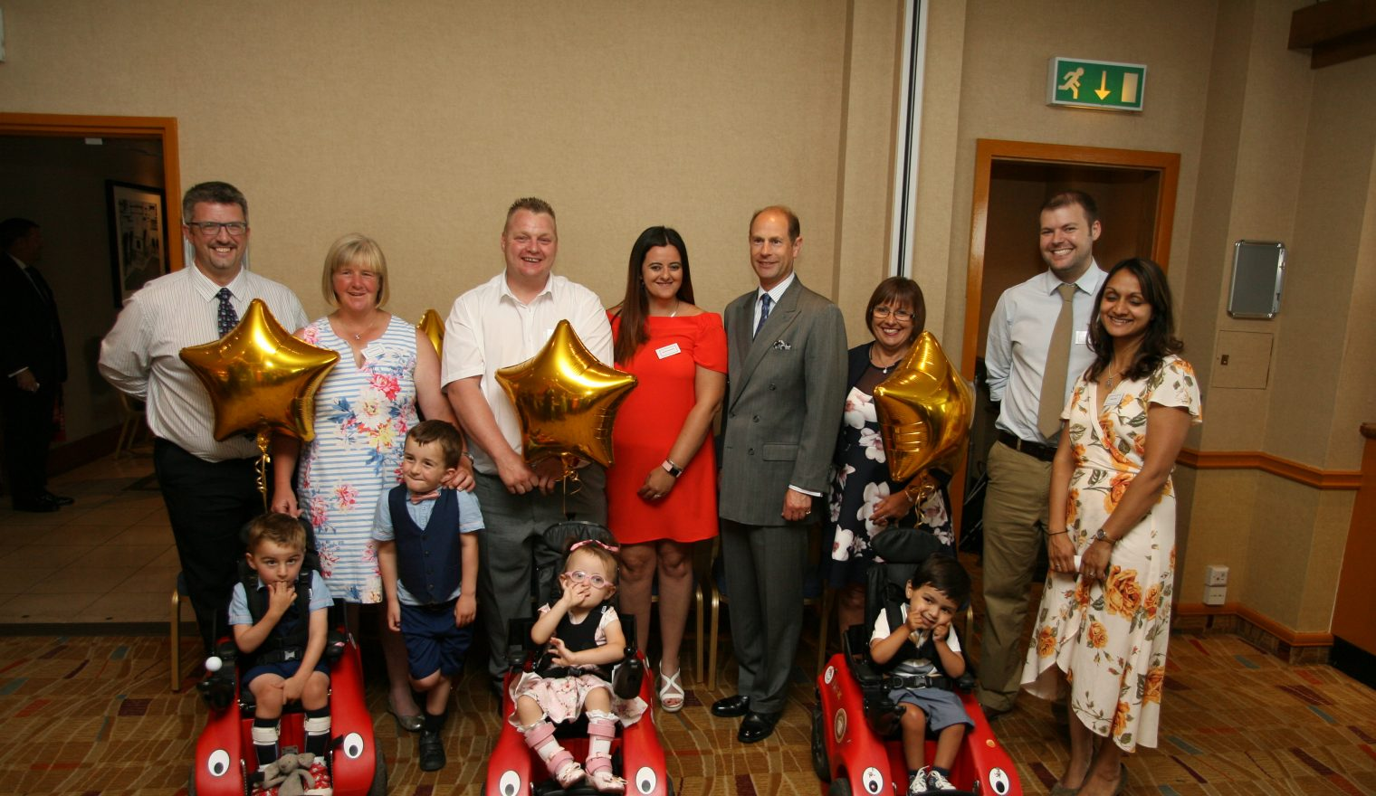 Three children in Wizzybug wheelchairs and their families in a picture with Prince Edward