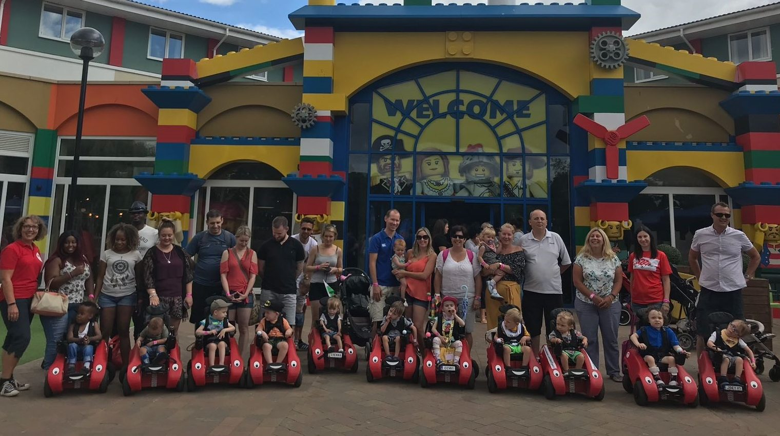 Lots of families standing together with children in Wizzybug wheelchairs at the entrance to Legoland