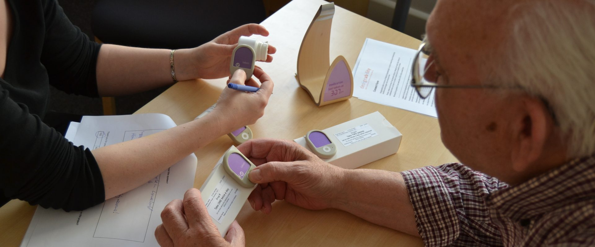 A close-up of people's hands holding a medicine reminder system