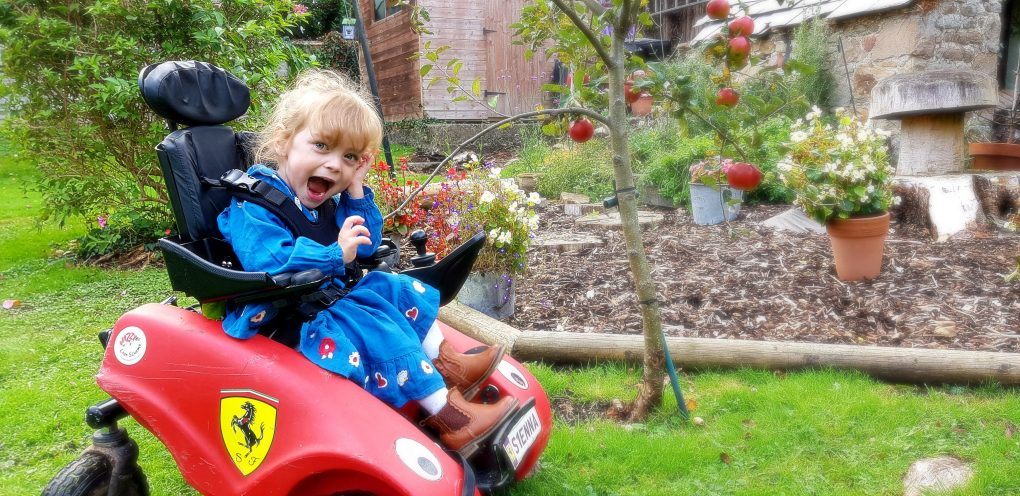 Young girl in a Wizzybug wheelchair in the garden