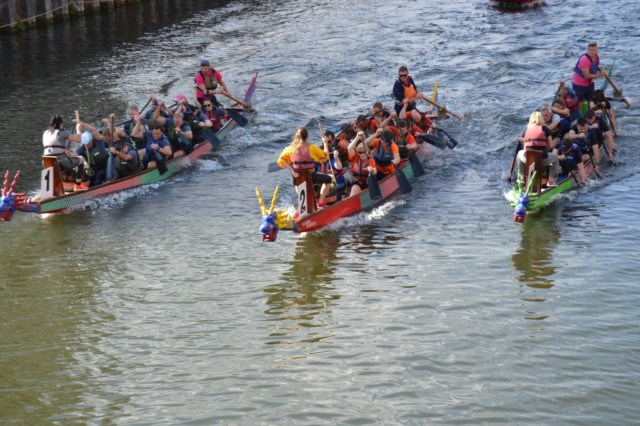 Three dragon boats racing down a river