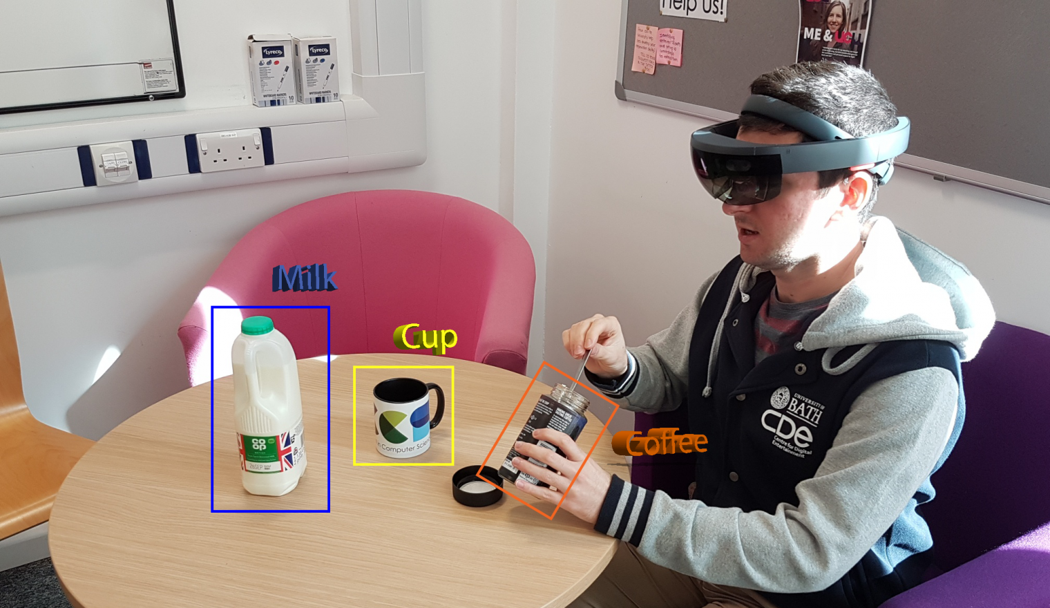 A man sat at a table making a cup of coffee using augmented reality technology