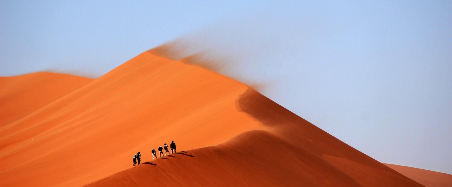People trekking across a sand dune
