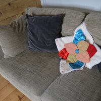 An open Bud sensory cushion arranged with other cushions on a sofa