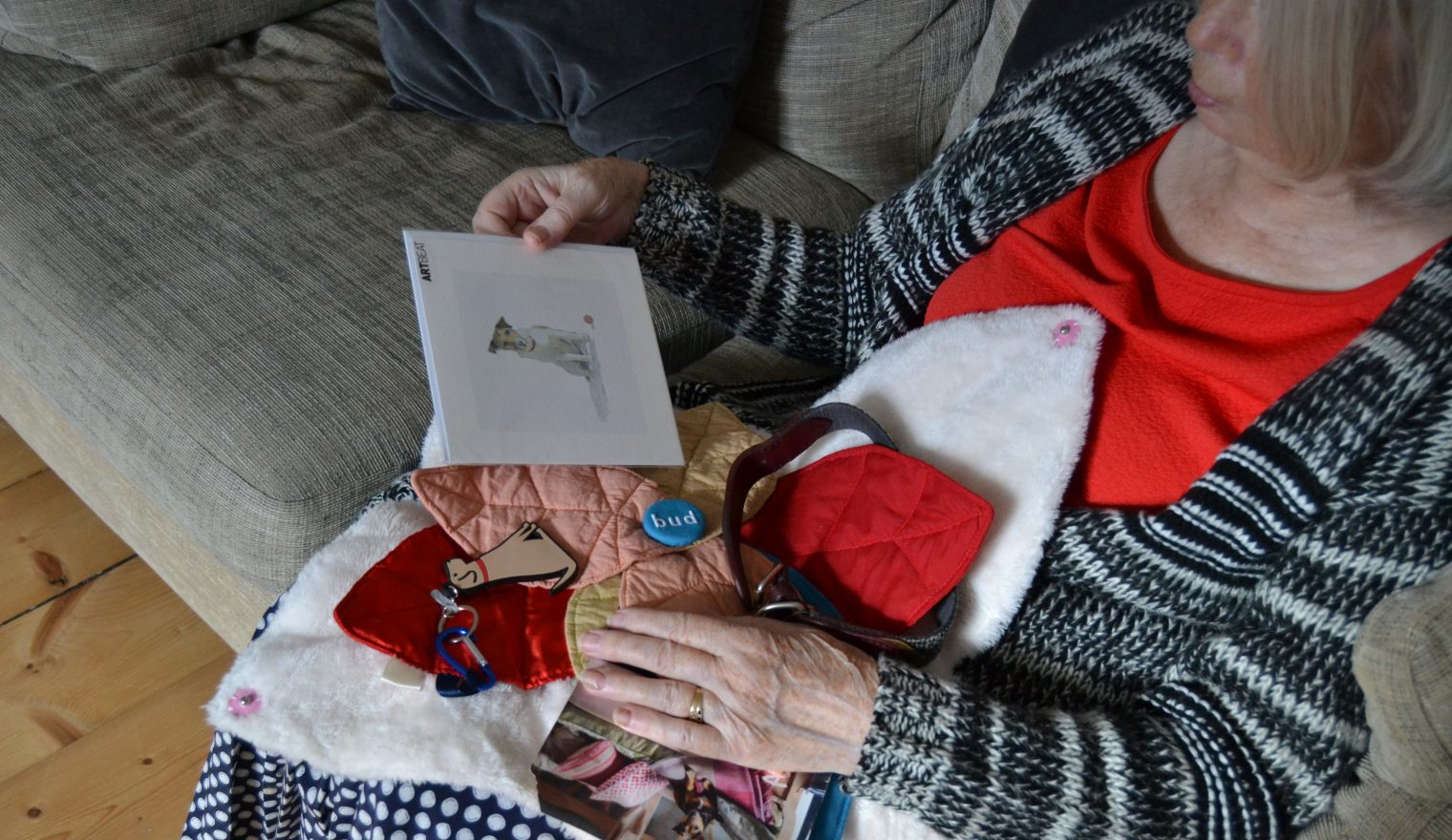 A woman sat on a sofa looking at a picture of a dog from her Bud sensory cushion