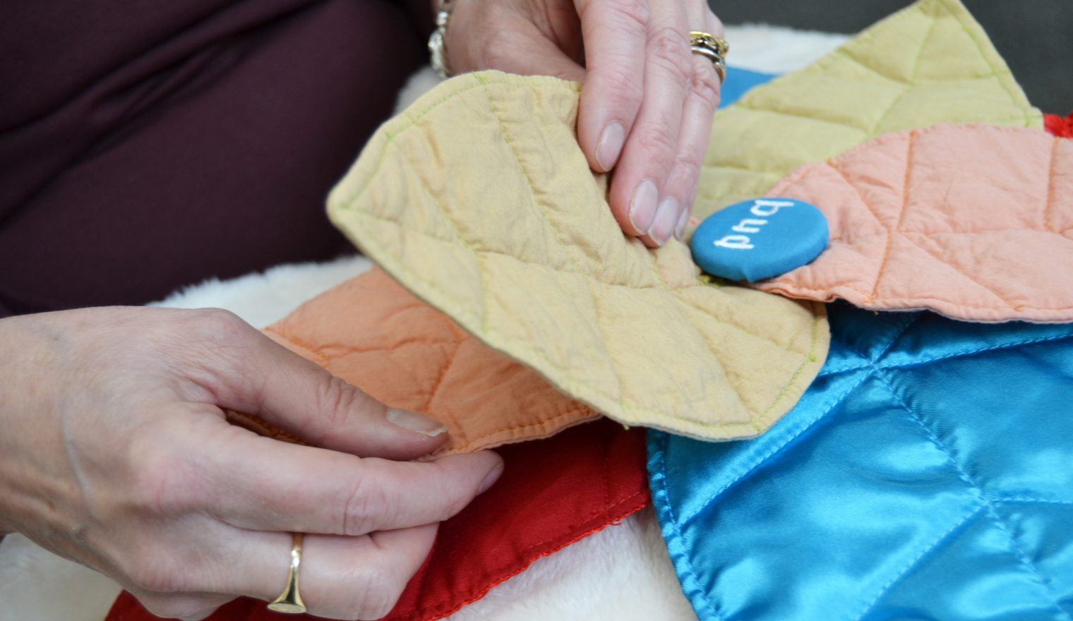 Two hands rearranging the fabric petals on a Bud sensory cushion