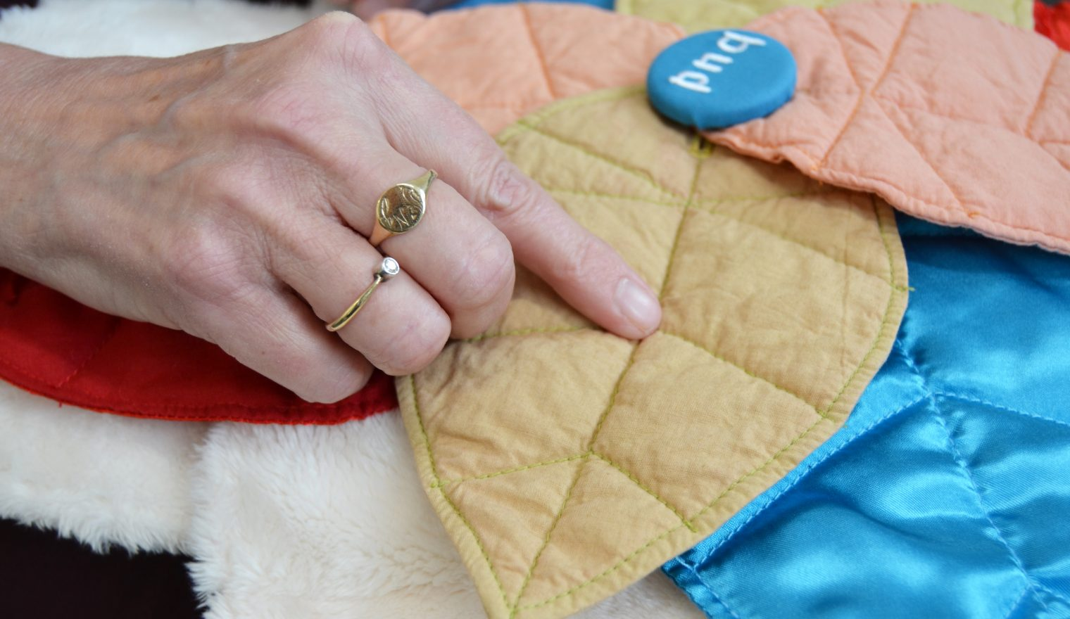 A hand tracing the leaf stitching on a Bud sensory cushion