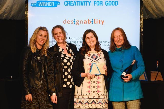 Four women smiling at camera holding award