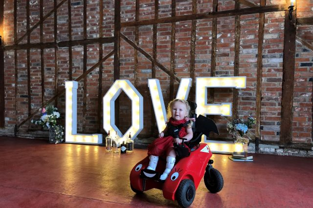 Young girl in Wizzybug powered wheelchair on dance floor in front of LOVE letters