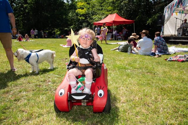 Young girl in Wizzybug powered wheelchair outdoors with face paint and a fairy wand