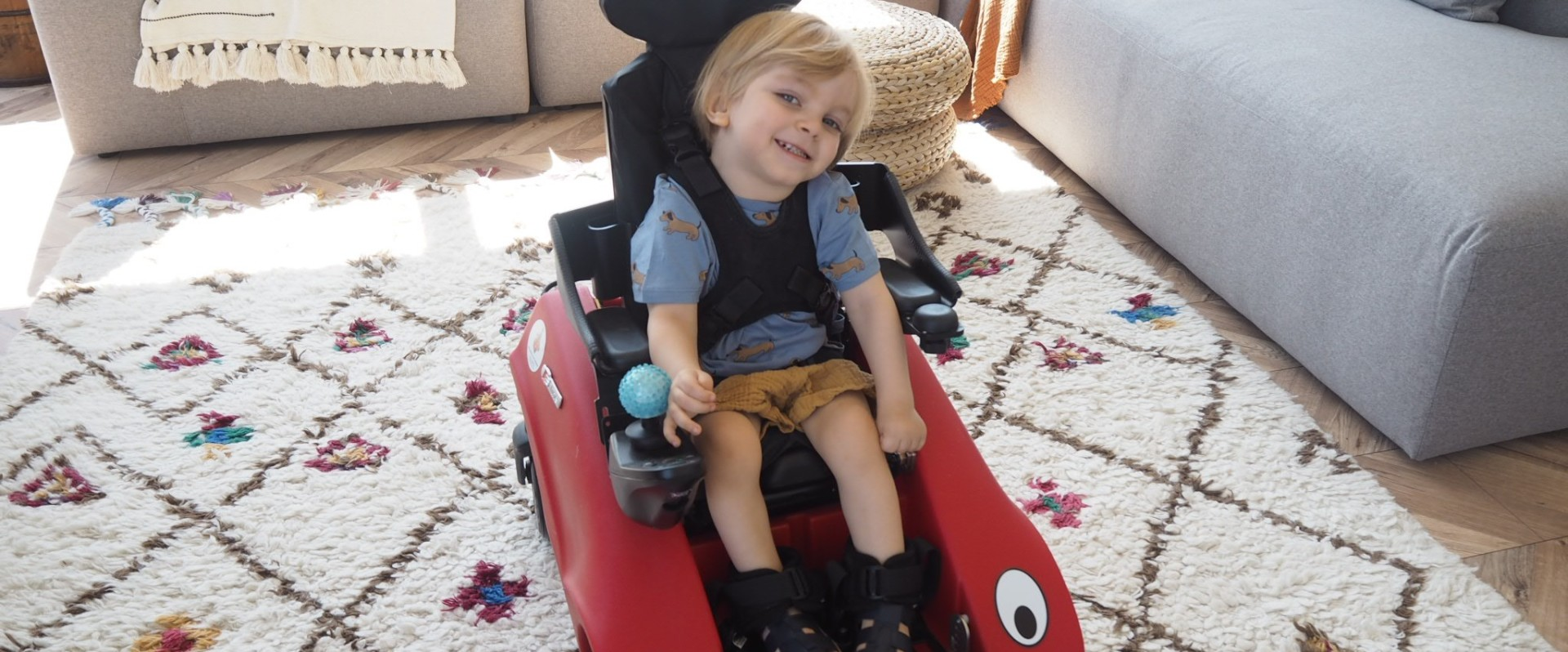 Young boy smiling in Wizzybug powered wheelchair in a living room