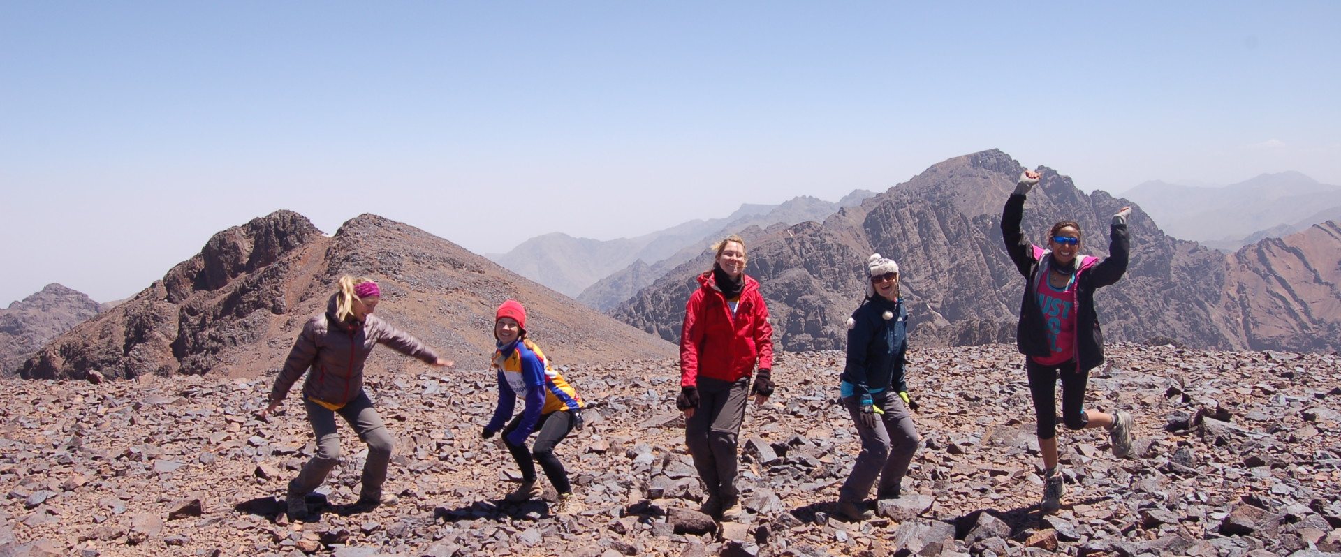 Four people jumping in the air in the Atlas Mountains