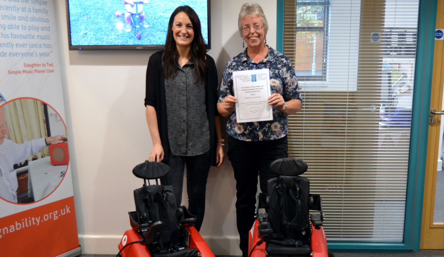 Two women holding a certificate smiling at camera with two Wizzybug powered wheelchairs
