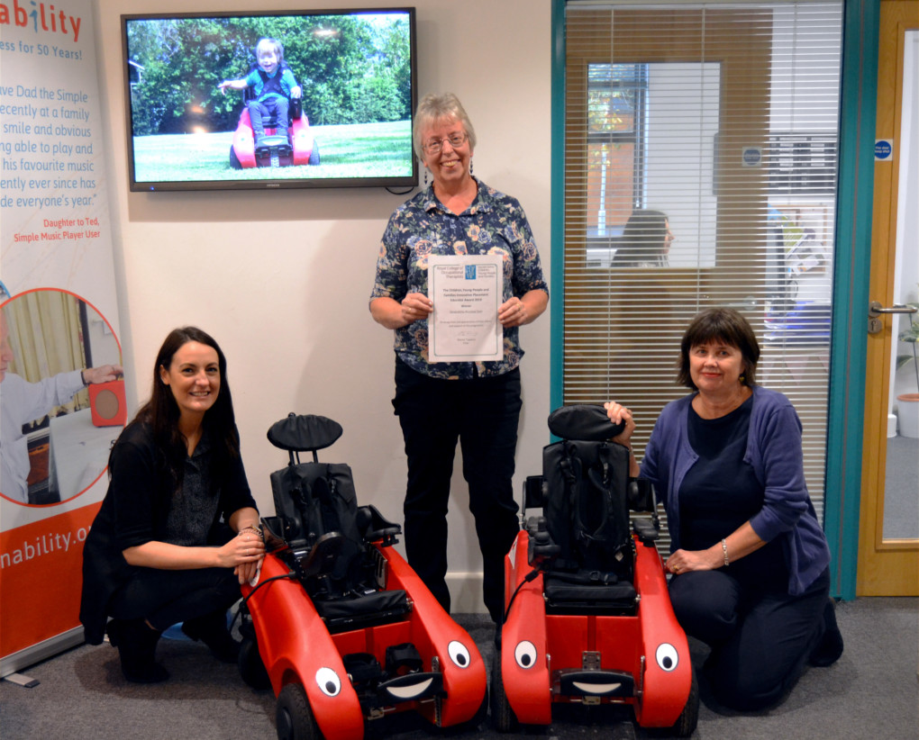 Three women posing with Wizzybug powered wheelchairs and holding a certificate