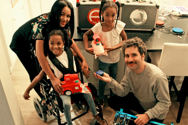 Designer crouched by a family with daughter in wheelchair holding switch toy