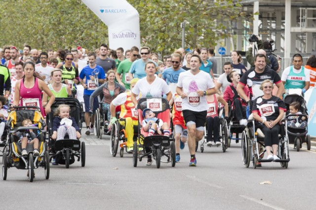 Group of people running and pushing pushchairs and wheelchairs on a street