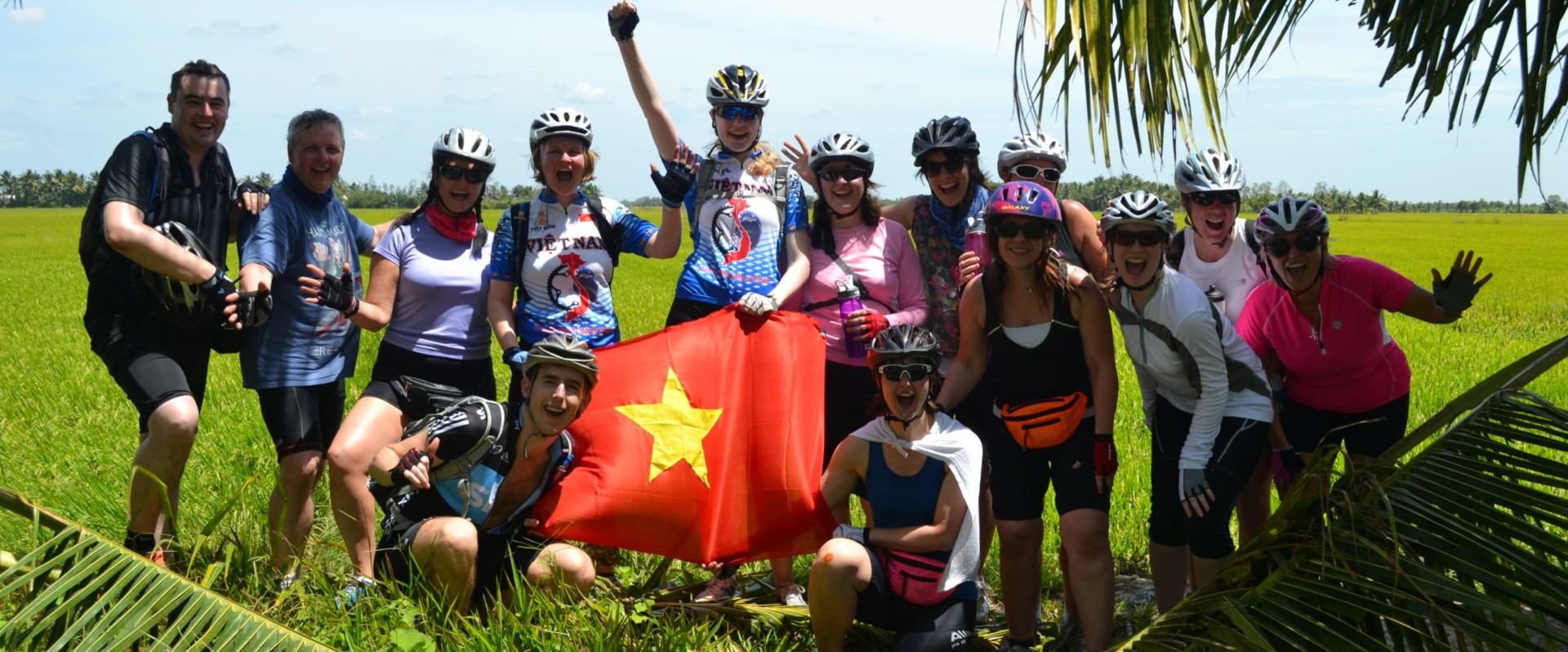 Group of people in cycling jerseys, holding flag, smiling