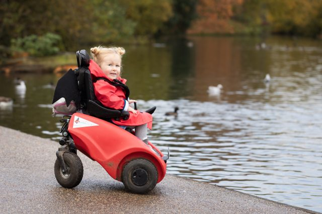 Young child in a Wizzybug powered wheelchair by a duck pond