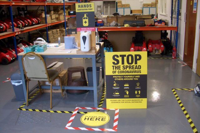 Workshop entrance with Coronavirus signage and safety markings