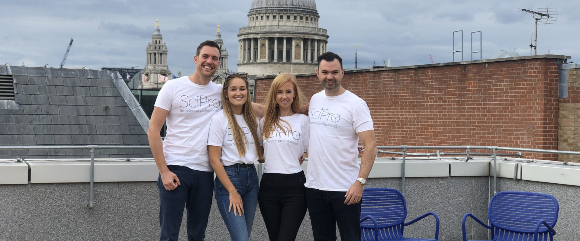 Group of people stood on a rooftop, wearing SciPro t-shirts, smiling at camera