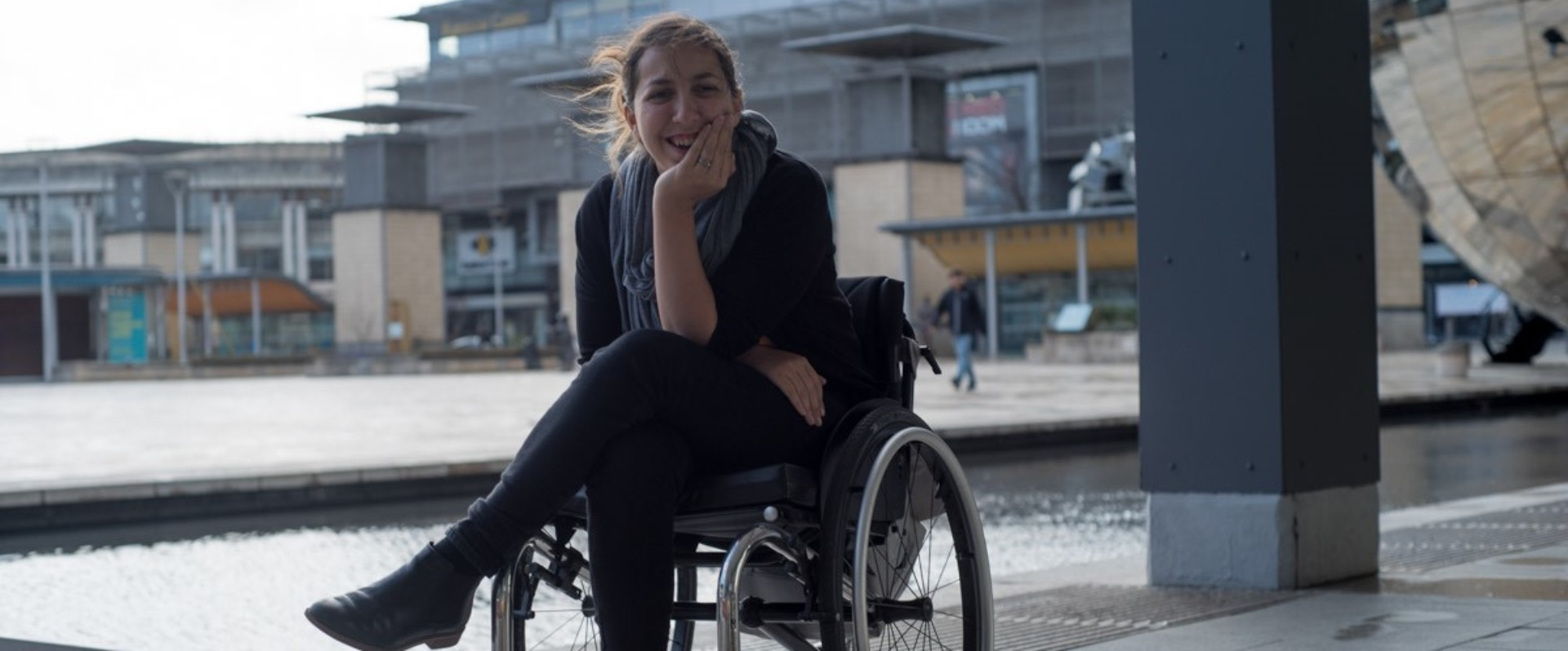 Person sat in manual wheelchair, leaning face on one hand, smiling, outside
