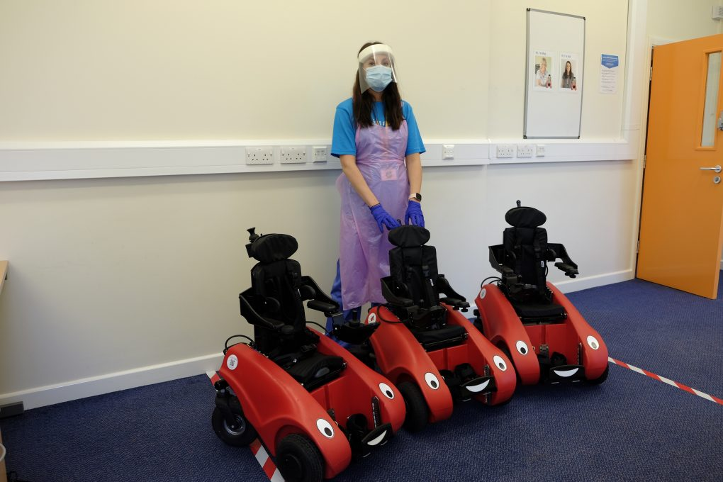 Occupational therapist stood in full PPE behind three Wizzybug powered wheelchairs