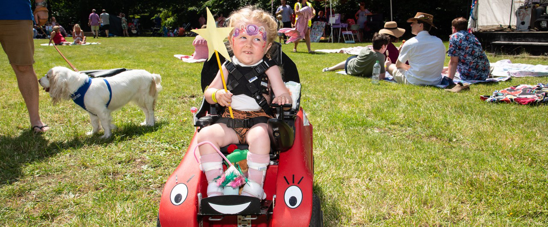 Young girl in Wizzybug powered wheelchair, in a park, wearing face paint and holding fairy wand