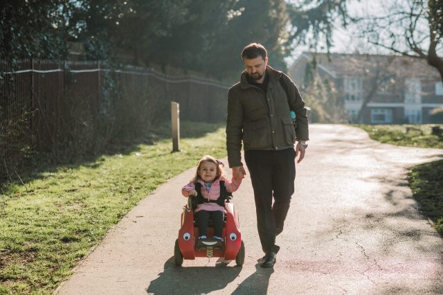 Young girl in Wizzybug wheelchair holding her dad's hand in the park